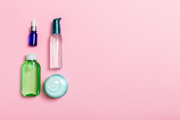 Marca de cosméticos spa, vista superior com copyspace. conjunto de tubos e potes de creme plana leigos em fundo rosa