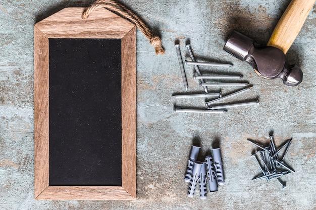 Marca de madeira em branco, martelo, parafusos, pregos e plugue de parede na mesa de madeira enferrujada