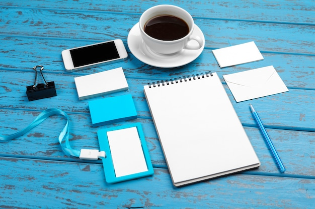 Marca de papelaria na mesa azul. vista superior do papel, cartão de visita, bloco, canetas e café.