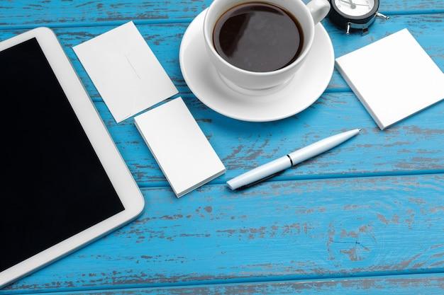 Marca de papelaria na mesa azul.