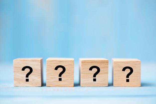 Marca de perguntas no bloco de cubo de madeira