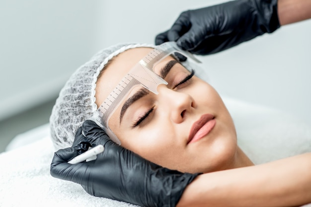 Marcação com régua nas sobrancelhas da mulher yong durante a maquiagem definitiva.