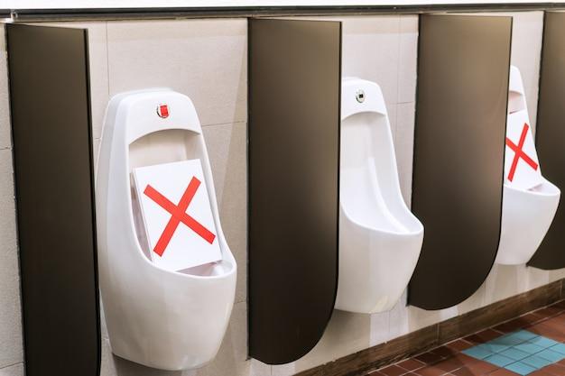 Marcação de uso da alternativa para regras de distância social do vaso sanitário no banheiro. medidas de proteção pandêmica. conceito de distanciamento social