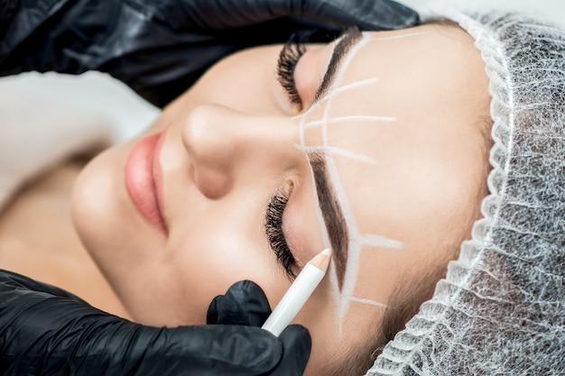Marcação nas sobrancelhas de uma jovem com lápis durante a maquiagem permanente.