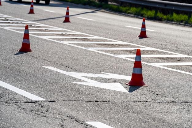 Marcações de carros no asfalto com cones, placas para controlar a direção do movimento