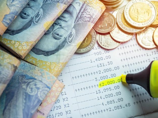 Marcador amarelo de close-up destacando o dinheiro do depósito, extrato da conta na caderneta da conta poupança com dinheiro