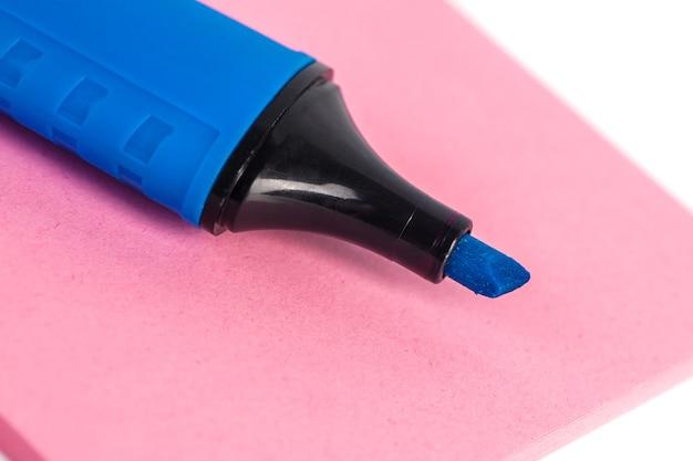 Marcador azul e papel em um fundo branco.