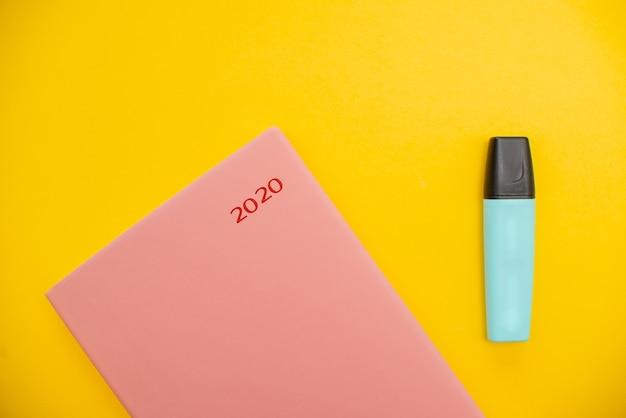 Marcador e bloco de notas em um fundo abstrato amarelo com espaço da cópia, estilo mínimo.