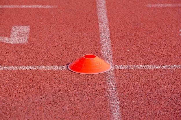 Marcador laranja na pista de corrida para o fundo de atletas
