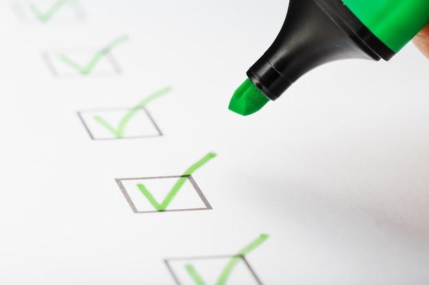 Marcador verde com marcadores na folha da lista de verificação. conceito de tarefa concluída da lista de verificação.