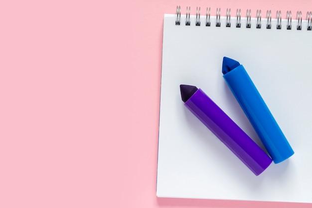 Marcadores azuis e violetas em uma folha branca de um quadro negro com uma espiral