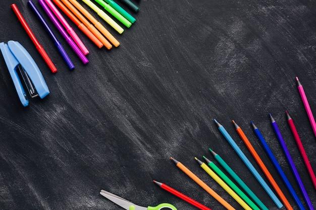 Marcadores coloridos e lápis em fundo cinza