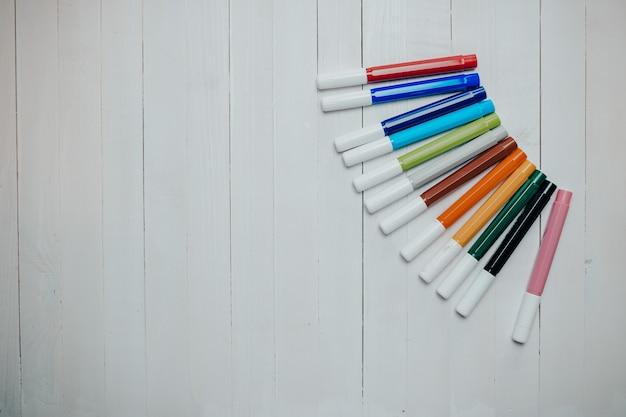 Marcadores coloridos e tintas no fundo branco