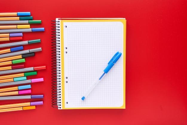 Marcadores coloridos e um caderno sobre um fundo vermelho. voltar ao conceito de escola e artesanato.