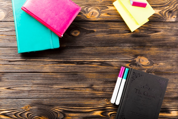 Marcadores e cadernos na mesa de madeira