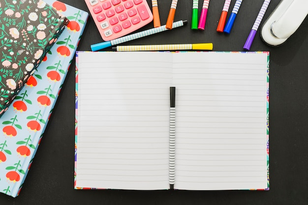 Marcadores e papel branco com calculadora e grampeador