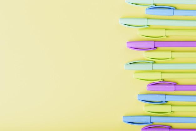Marcadores multicoloridos em amarelo com espaço livre.