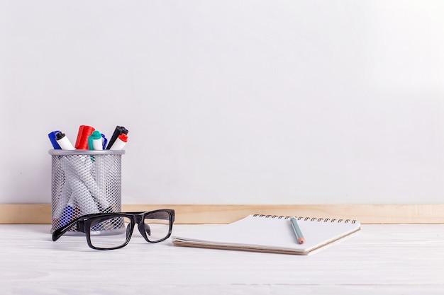 Marcadores, óculos, caderno, lápis e quadro branco.