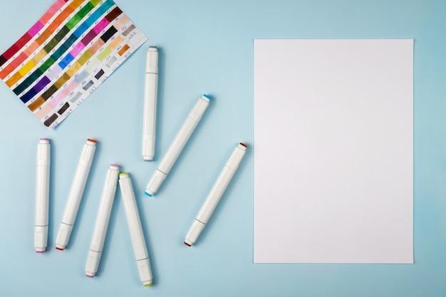 Marcadores para desenhar e uma folha de papel branca sobre um fundo azul.
