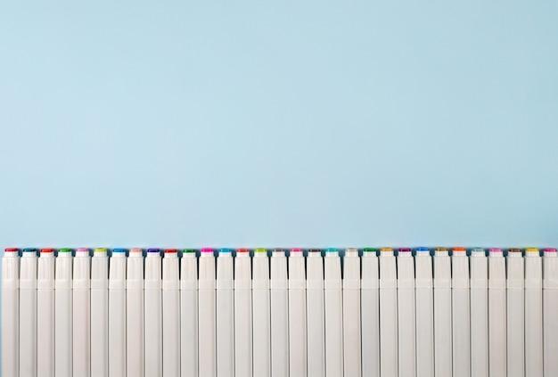 Marcadores para desenhar em um fundo azul.