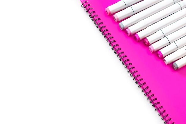 Marcadores profissionais multicoloridos estão em uma pasta rosa