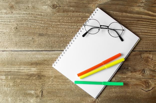 Marcadores verdes e alaranjados, um caderno e vidros em um fundo de madeira.