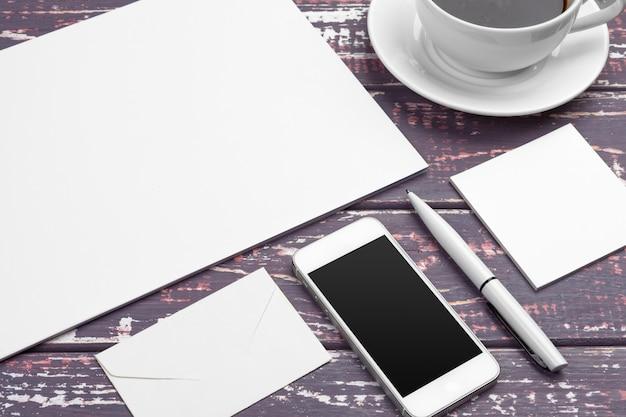 Marcando a maquete de artigos de papelaria na mesa roxa. vista superior do papel, cartão de visita, bloco, canetas e café.