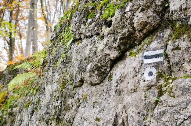 Marcando a rota turística pintada na pedra. sinal de rota de viagem.