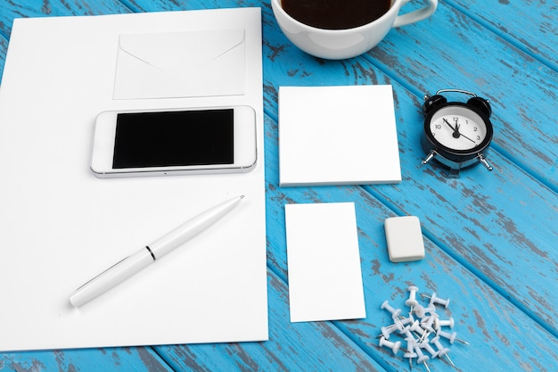 Marcando o modelo dos artigos de papelaria na mesa azul. vista superior do papel, cartão de visita, almofada, canetas e café.