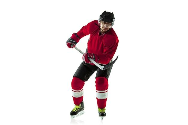 Marcar um gol. jogador de hóquei masculino com o taco na quadra de gelo e parede branca. desportista usando equipamento e praticando capacete. conceito de esporte, estilo de vida saudável, movimento, movimento, ação.