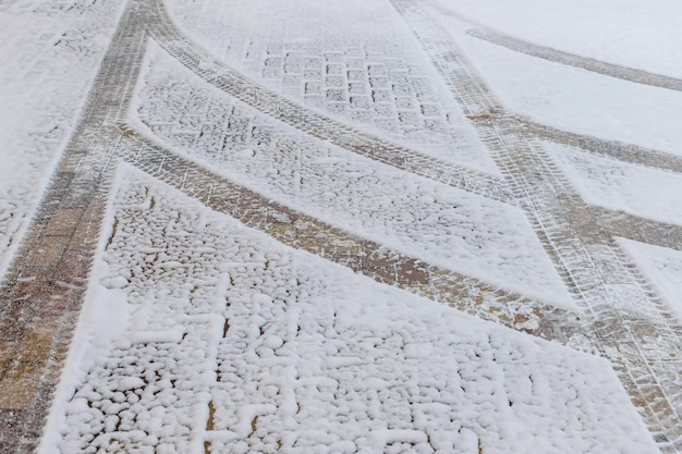Marcas curvas de pneus na neve na estrada