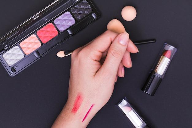 Marcas de batom na mão da fêmea com produtos cosméticos em fundo preto