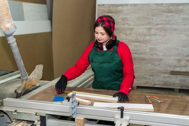 Marceneiro bonito de uniforme medindo prancha de madeira