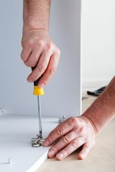 Marceneiro coleta móveis usando uma chave de fenda de ferramentas manuais. montagem de móveis com chave de fenda. mudança, reforma, reforma e reforma de móveis. carpenter coleta um armário de móveis brancos.