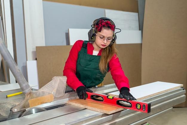 Marceneiro de mulher bonita em uniforme medindo prancha de madeira