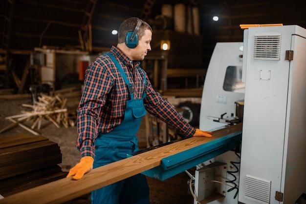 Marceneiro de uniforme e fones de ouvido trabalha em máquina para marcenaria, indústria madeireira, carpintaria. processamento de madeira na fábrica