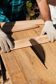 Marceneiro que trabalha duro cortando prancha de madeira, foco na serra