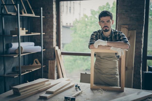 Marceneiro sério e confiante com uniforme de luvas apoiado em moldura feita à mão, olhando para você pensativamente com tábuas e ferramentas na mesa de lona