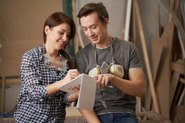 Marceneiros masculinos e femininos sorridentes com um caderno nas mãos na oficina