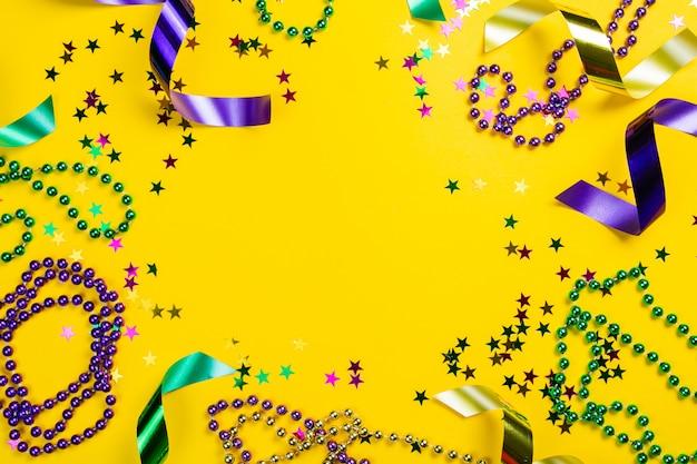 Mardi gras carnaval conceito - grânulos em fundo amarelo, vista superior