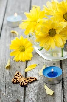 Margarida amarela fresca flores, borboleta e vela acesa
