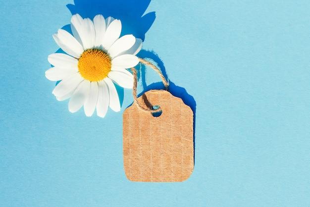 Margarida branca sobre um fundo azul com uma etiqueta. conceito de vendas de verão, compras de verão