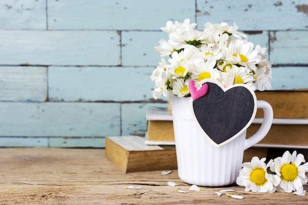 Margarida flores em copo branco com coração de madeira em branco