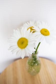 Margarida flores em um vaso em uma mesa de madeira.