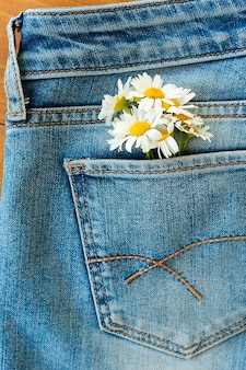 Margarida flores sem costura padrão em fundo de calça jeans.