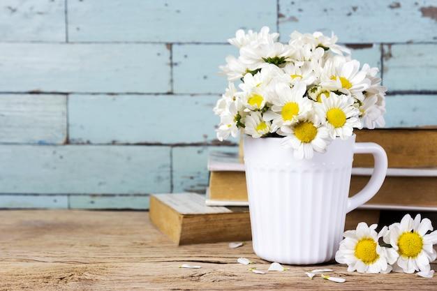 Margarida fresca flores em copo branco na mesa de madeira