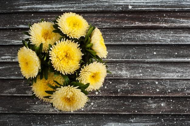 Margaridas amarelas sobre fundo de madeira