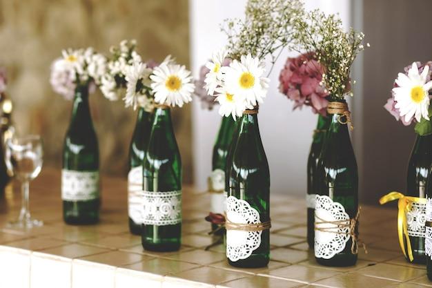 Margaridas brancas e hortênsias roxas em garrafas transparentes de vidro verde alto, buquês decorativos em vasos.