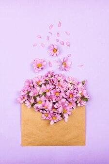 Margaridas cor de rosa em um envelope marrom vintage