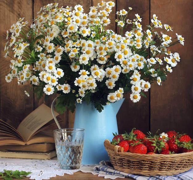 Margaridas em um frasco azul, em um livro aberto e em uma cesta das morangos na tabela, ainda vida rústica.